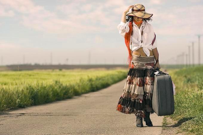 mulher-andando-pela-estrada-com-mala-na-m-c3-a3o