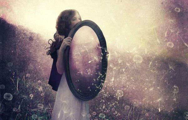 mulher-segurando-espelho-com-as-mc3a3os