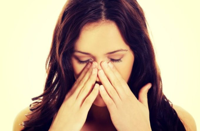 Young woman with sinus pain.